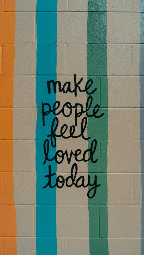 """Image of white brick wall with yellow, blue, and green vertical strips. It has text that reads """"make people feel loved today"""""""